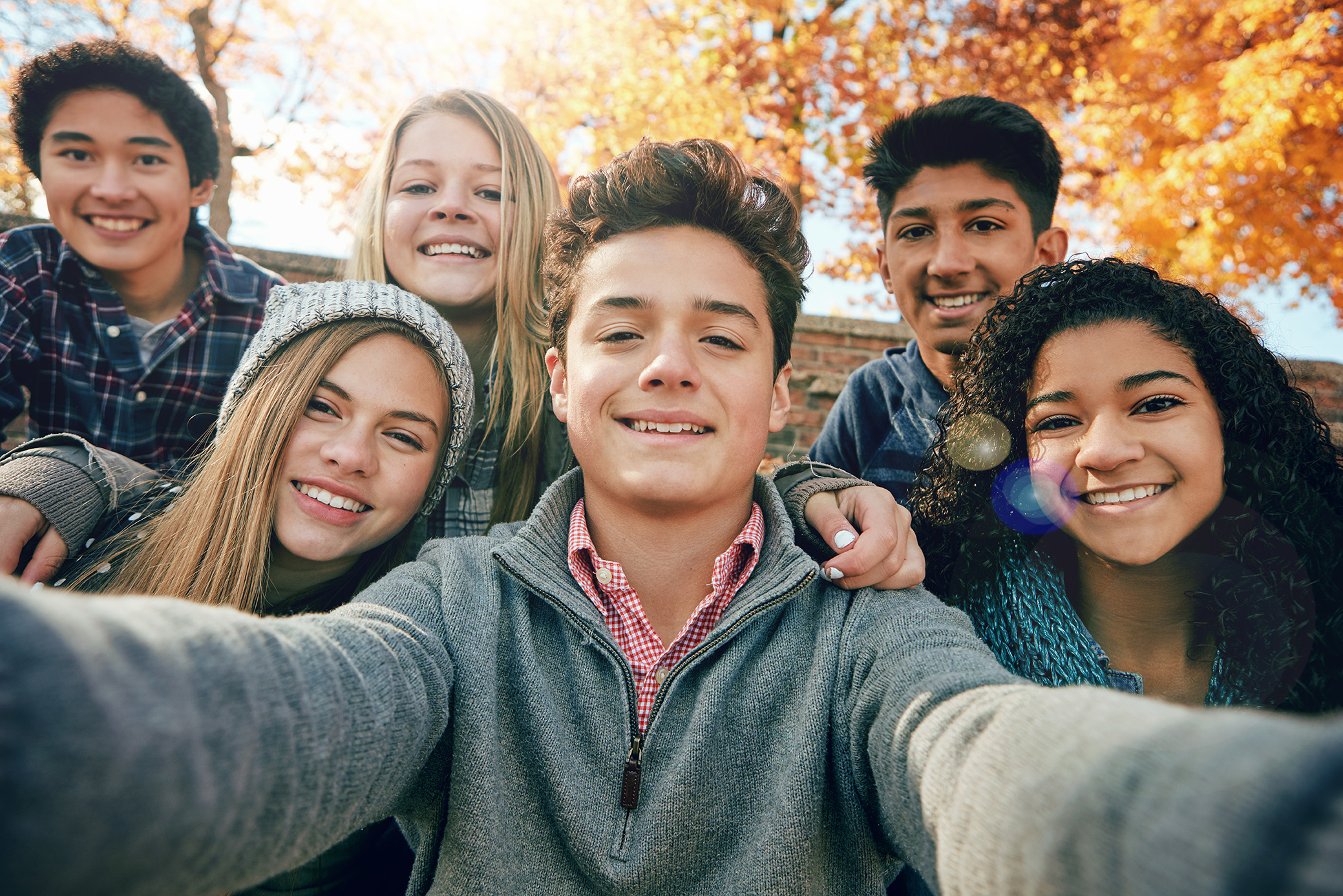Portrait of a group of young friends posing for a selfie together outside